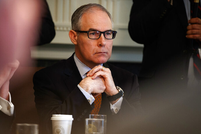 FILE - In this June 21, 2018, file photo, then-Environmental Protection Agency administrator Scott Pruitt listens as President Donald Trump speaks during a cabinet meeting at the White House in Washington. Pruitt, the scandal-plagued former chief of the EPA is denying he got any improper gifts on the job. The EPA on Wednesday, Sept. 12, released Pruitt's financial disclosure report for 2017. The report requires Pruitt to disclose sources of income and any gifts.(AP Photo/Evan Vucci, File)
