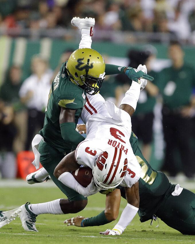 South Florida defensive back Mike Hampton upends Wisconsin wide receiver Kendric Pryor after a catch during the first half of an NCAA college football game Friday, Aug. 30, 2019, in Tampa, Fla. (AP Photo/Chris O'Meara)