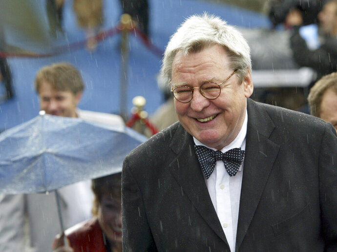 """FILE - Film director Alan Parker arrives at the opening ceremony of 26th Moscow International Film Festival in Moscow on June 18, 2004. Parker, whose movies included """"Bugsy Malone,"""" """"Midnight Express"""" and """"Evita,"""" has died at the age of 76. A statement from the director's family says Parker died Friday in London after a long illness. (AP Photo/Misha Japaridze, File)"""