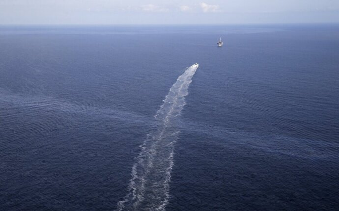 "FILE - In this March 31, 2015 file photo, the wake of a supply vessel heading towards a working platform crosses over an oil sheen drifting from the site of the former Taylor Energy oil rig in the Gulf of Mexico, off the coast of Louisiana. The Coast Guard says a newly installed containment system is collecting oil at the site of the 14-year-old oil leak in the Gulf of Mexico.  A Coast Guard statement Thursday, May 16, 2019, describes the installation of the subsea containment system as a ""major milestone"" in the federal government's long-running efforts to contain the leak.   (AP Photo/Gerald Herbert, File)"