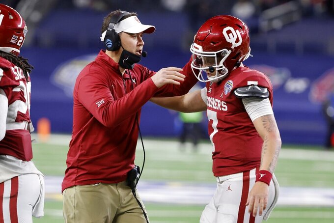 FILE - In this Dec. 30, 2020, file photo, Oklahoma coach Lincoln Riley, left, celebrates with quarterback Spencer Rattler after Rattler ran for a touchdown against Florida during the Cotton Bowl NCAA college football game in Arlington, Texas. Riley understands why there's so much buzz surrounding his second-ranked Sooners. He just doesn't care. Oklahoma's high-powered offense returns Rattler and plenty of other talent from a 9-2 squad. That's why the Sooners have the program's highest preseason ranking since 2011. Now, it's time to play. Oklahoma hosts Tulane on Saturday in a season-opening contest that was moved from New Orleans because of Hurricane Ida. (AP Photo/Michael Ainsworth, File)