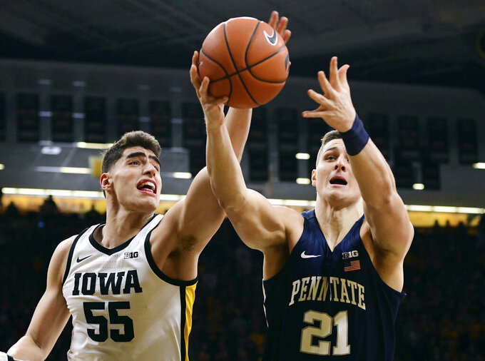 Iowa's Luka Garza (55) and Penn State's John Harrar reach for a rebound during the first half of an NCAA college basketball game, Saturday, Feb. 29, 2020, in Iowa City, Iowa. (AP Photo/Cliff Jette)