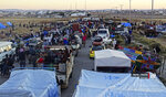 FILE - This  June 30, 2018 file photo provided by Nabaa Media, a Syrian opposition media outlet, shows people in their vehicles who fled from Daraa, gathering near the Syria-Jordan border. Syrian activists and state media said Thursday, July 12, 2018 that the rebels have agreed to surrender Daraa, the first city to revolt against President Bashar Assad with Arab Spring-inspired protests seven years ago, to government forces. (Nabaa Media, via AP, File)