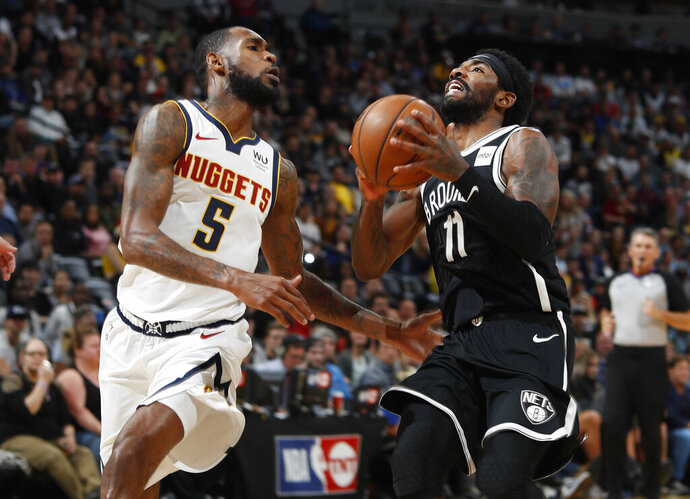 Denver Nuggets forward Will Barton left, defends as Brooklyn Nets guard Kyrie Irving drives to the rim in the second half of an NBA basketball game Thursday, Nov. 14, 2019 in Denver. The Nuggets won 101-93. (AP Photo/David Zalubowski)