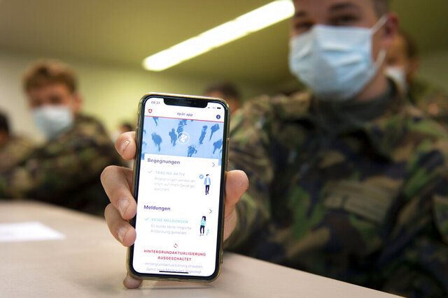 A soldier of the Swiss army wearing a protective face mask holds a smartphone with an app using Decentralized Privacy-Preserving Proximity Tracing (DP-3T) during a test with 100 soldiers in the military compound of Chamblon near Yverdon-les-Bains, Switzerland, Thursday, April 30, 2020. The race by governments to develop mobile tracing apps in order to contain infections after lockdowns ease is focusing attention on privacy. The debate is especially urgent in Europe, where academics and civil liberties activists are pushing for solutions that protect personal data. (Laurent Gillieron/Keystone via AP)