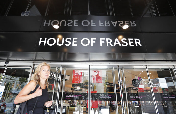 A woman walks past the House of Fraser department store on Oxford Street in London, Friday, Aug. 10, 2018.  British retailer Sports Direct said Friday that it has bought struggling department store chain House of Fraser, just hours after the 169-year-old business went into administration. (AP Photo/Frank Augstein)