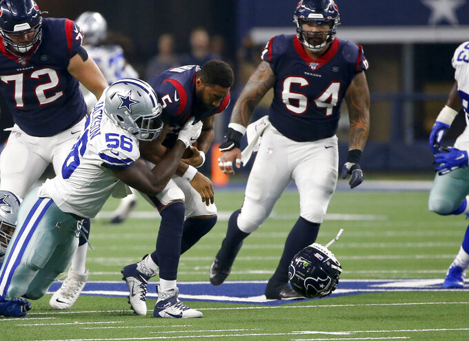 Dallas Cowboys defensive end Joe Jackson (56) sacks Houston Texans' Joe Webb (5) who loses his helmet on the stop as Texans' Rick Leonard (72) and Senio Kelemete (64) look on in the first half of a preseason NFL football game in Arlington, Texas, Saturday, Aug. 24, 2019. (AP Photo/Ron Jenkins)