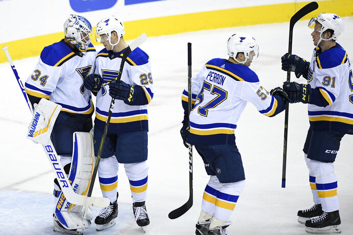 St. Louis Blues goaltender Jake Allen (34), defenseman Vince Dunn (29), right wing Vladimir Tarasenko (91), of Russia, and left wing David Perron (57) celebrate after an NHL hockey game against the Washington Capitals, Monday, Jan. 14, 2019, in Washington. The Blues won 4-1. (AP Photo/Nick Wass)