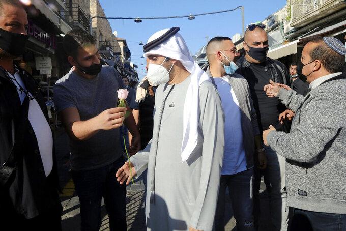 An Israeli man handed a flower to Emirati singer Walid Aljasim, during his visit in Jerusalem, Thursday, Dec. 3, 2020. (AP Photo/Mahmoud Illean)