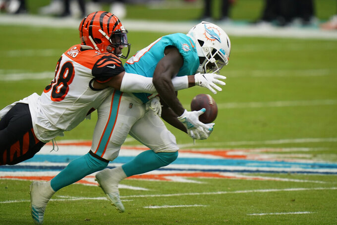 Cincinnati Bengals cornerback LeShaun Sims (38) defends Miami Dolphins wide receiver Jakeem Grant (19) as Grant is unable to hold onto the football, during the first half of an NFL football game, Sunday, Dec. 6, 2020, in Miami Gardens, Fla. (AP Photo/Wilfredo Lee)