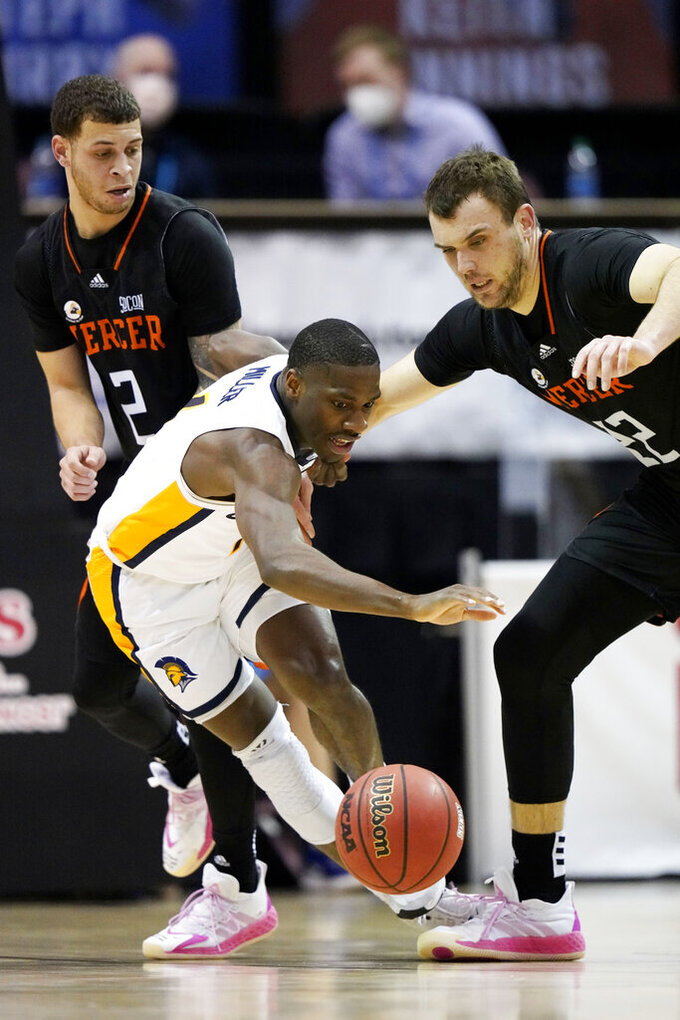 UNC-Greensboro guard Isaiah Miller (1), Mercer guard Neftali Alvarez (2) and Mercer forward Felipe Haase (22) scramble for the ball in the first half of an NCAA men's college basketball championship game for the Southern Conference tournament, Monday, March 8, 2021, in Asheville, N.C. (AP Photo/Kathy Kmonicek)