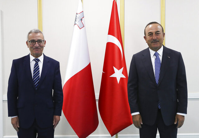 Turkey's Foreign Minister Mevlut Cavusoglu, right, and Evarist Bartolo, Minister for Foreign and European Affairs of the Republic of Malta, pose for photos before a meeting, in Ankara Turkey, Tuesday, July 14, 2020.(Cem Ozdel/Turkish Foreign Ministry via AP, Pool)
