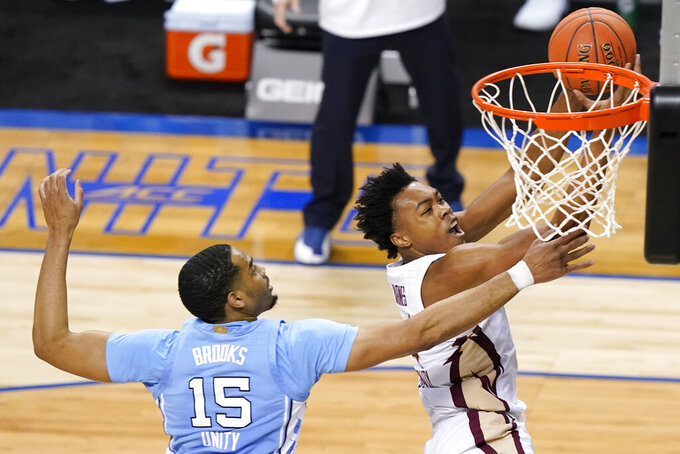 Florida State guard Scottie Barnes, right, is fouled as he shoots by North Carolina forward Garrison Brooks (15) during the first half of an NCAA college basketball game in the semifinal round of the Atlantic Coast Conference tournament in Greensboro, N.C., Friday, March 12, 2021. (AP Photo/Gerry Broome)