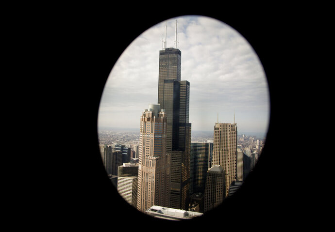 FILE - In this April 2, 2014, file photo, the Willis Tower, in downtown Chicago is seen through the window of an Osprey helicopter traveling with President Barack Obama. The famed skyscraper on Thursday, Dec. 19, 2019, became the largest building in the nation to earn the highest level of energy efficiency. Building owner Equity Office, the U.S. office arm of private-equity giant Blackstone Group, made the announcement that the 110-story skyscraper reached the Leadership in Energy and Environmental Design, or LEED, Platinum certification, the Chicago Tribune reported. (AP Photo/Carolyn Kaster, File)