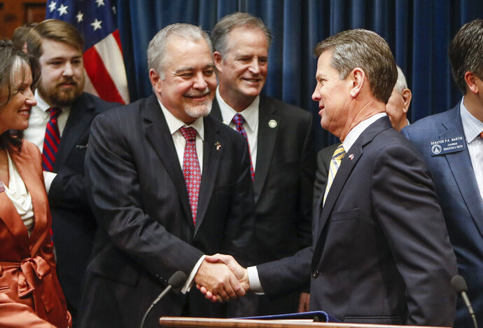 Gov. Brian Kemp greets state school Superintendent Richard Woods as he entered his ceremonial office where he announced legislation to cut five mandatory standardized tests for Georgia public school students, including four in high school, during a news conference, Tuesday, Feb. 4, 2020 in Atlanta.  The Republican officials are also trying to cut the length of state tests and evaluate local tests that Georgia's 181 school districts give to evaluate student progress.  (Bob Andres /Atlanta Journal-Constitution via AP)