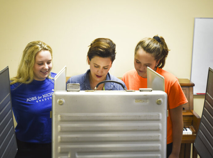 Flanked by daughters Sydney Shrewsbury, 14, left, and 11-year-old Sherry, Michigan democratic gubernatorial candidate Gretchen Whitmer fills out her ballot, Tuesday, Aug. 7, 2018, at St. Paul Lutheran church in East Lansing, Mich. (Matthew Dae Smith/Lansing State Journal via AP)