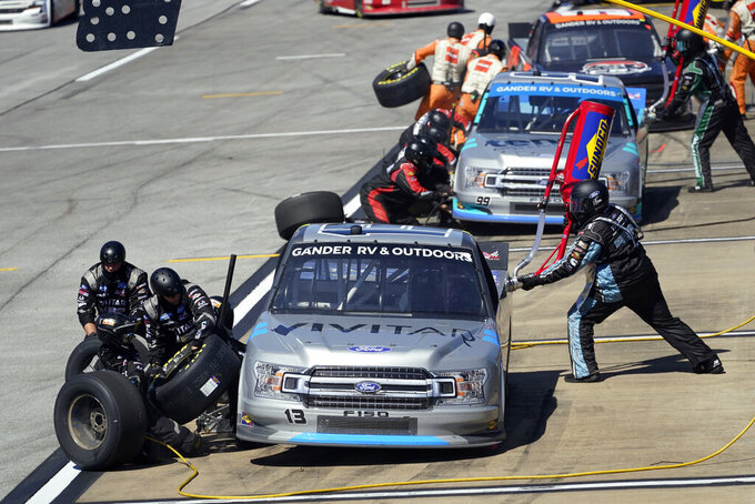 Pit crews work to change tires and refuel Johnny Sauter (13) and Ben Rhodes (99) during the NASCAR Truck series auto race at Talladega Superspeedway, Saturday, Oct. 3, 2020, in Talladega, Ala.. (AP Photo/John Bazemore)