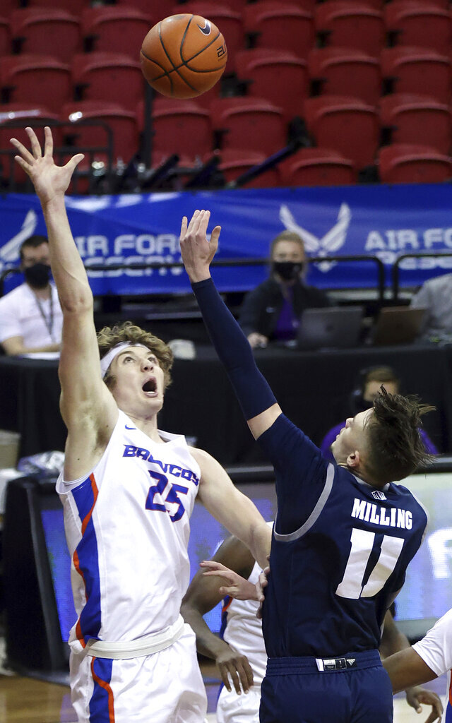 Nevada guard Kane Milling (11) shoots as Boise State center Lukas Milner (25) defends during the first half of an NCAA college basketball game in the quarterfinals of the Mountain West Conference men's tournament Thursday, March 11, 2021, in Las Vegas. (AP Photo/Isaac Brekken)