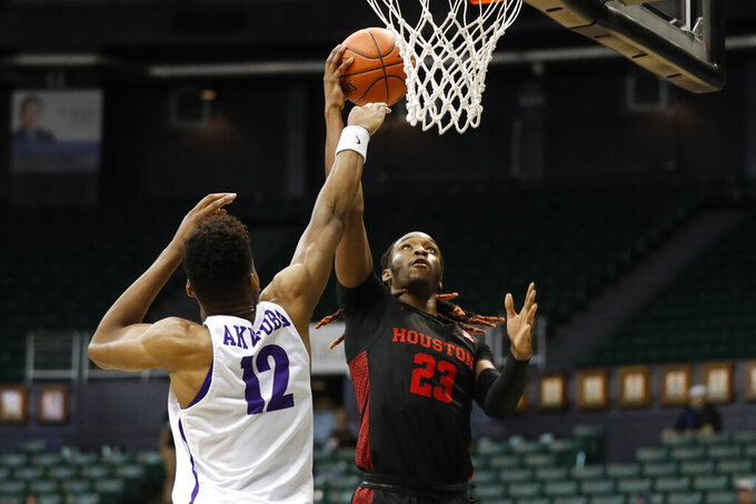 Houston forward Cedrick Alley Jr. (23) shoots over Portland center Theo Akwuba (12) during the second half of an NCAA college basketball game Sunday, Dec. 22, 2019, in Honolulu. (AP Photo/Marco Garcia)