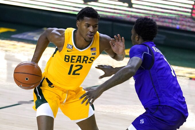 Baylor's Jared Butler (12) handles the ball as he works against Stephen F. Austin's DeAndre Heckard (1) duriing the first half of an NCAA college basketball game in Waco, Texas, Wednesday, Dec. 9, 2020. (AP Photo/Tony Gutierrez)