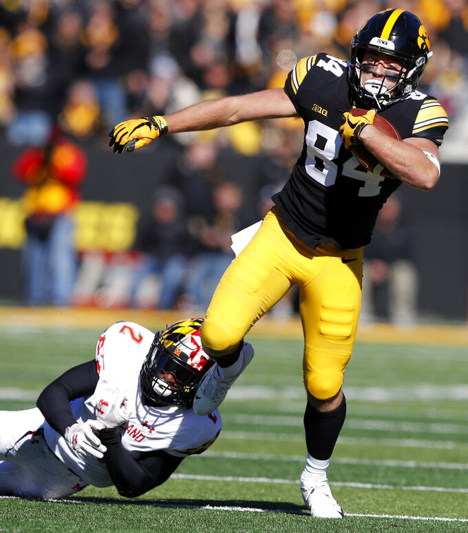 Iowa wide receiver Nick Easley breaks a tackle by Maryland defensive back RaVon Davis (2) after making a reception during the first half of an NCAA college football game, Saturday, Oct. 20, 2018, in Iowa City, Iowa. Iowa won 23-0. (AP Photo/Charlie Neibergall)