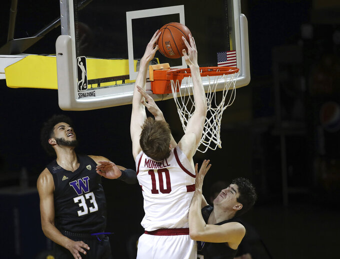 CORRECTS YEAR TO 2021 NOT 2020 - Stanford forward Max Murrell (10), center, dunks against Washington forward J'Raan Brooks (33), left, and center Riley Sorn (52), right, during the first half of an NCAA college basketball game in Santa Cruz, Calif., Thursday, Jan. 7, 2021. (AP Photo/Josie Lepe)