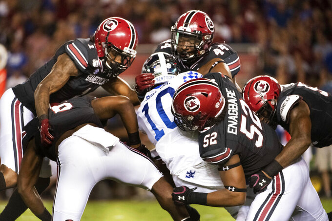 FILE - South Carolina defensive lineman Kingsley Enagbare (52), Sherrod Greene (44), Jaycee Horn (1) and T.J. Brunson (6) tackle Kentucky running back Asim Rose (10) during the second half of an NCAA college football game in Columbia, S.C. , in this Saturday, Sept. 28, 2019, file photo. Enagbare broke out in a big way for a Gamecocks team that went 2-8 in 2020, and he should thrive on the edge in new defensive coordinator Clayton White's 4-2-5 base alignment. (AP Photo/Sean Rayford, File)