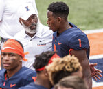 FILE - In this Sept. 1, 2018 file photo Illinois head coach Lovie Smith gives his quarterback A.J. Bush a pat on the back after an NCAA college football game against Kent State in Champaign, Ill. Wisconsin had had trouble against running quarterbacks, and their secondary is hampered by injuries. The mobile Bush, who has rushed for three scores over two games since returning from a hamstring injury, may have to wreak havoc in order for the Illini to have a chance at keeping the game close on Saturday, Oct. 20, 2018. (AP Photo/Holly Hart, file)