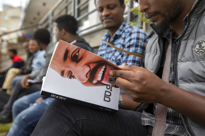 A man reads a new book by Prime Minister Dr Abiy Ahmed on MEDEMER (synergy) after it was launched Saturday Oct. 19, 2019, at the Ethiopian capital Addis Ababa. Ethiopia's Nobel Peace Prize-winning prime minister's book of his ideology, with one million copies already printed. Saturday's launch again raises concerns among some in the East African nation that a cult of personality could spring up around Prime Minister Abiy Ahmed, who announced sweeping political reforms after taking office last year. (AP Photo/Mulugeta Ayene)