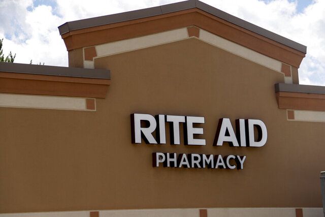 FILE - This June 25, 2019, file photo shows a sign for a Rite Aid Pharmacy is on the facade at a strip mall in Harmony, Pa. Rite Aid Corporation reports financial results on Thursday, Dec. 19. (AP Photo/Keith Srakocic, File)