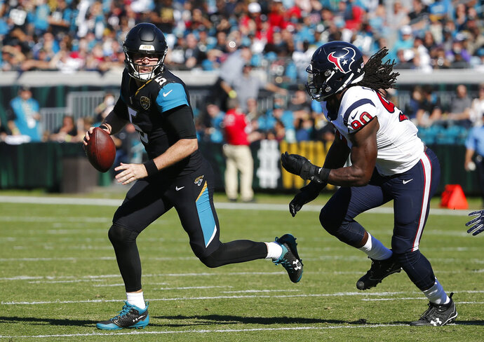 "FILE - In this Dec. 17, 2017, file photo, Jacksonville Jaguars quarterback Blake Bortles, left, looks for a receiver as he is pressured by Houston Texans defensive end Jadeveon Clowney (90) during the first half of an NFL football game, in Jacksonville, Fla. Clearly frustrated following a 45-7 loss at Jacksonville on Sunday, Clowney called Bortles trash after the game.""If how we're playing and how I'm playing is trash, then I'm fine with being trash,"" Bortles said Wednesday, Dec. 20.(AP Photo/Stephen B. Morton, File)"