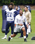 Dallas Cowboys running back Ezekiel Elliott (21) looks on as quarterback Dak Prescott warms-up during an NFL football team practice Tuesday, June 8, 2021, in Frisco, Texas. (AP Photo/LM Otero)