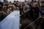 Comrades burry Said Abdel Ahad, a Christian fighter of the Syriac Military Council, during his funeral in Hassakeh, Syria, Friday, Nov. 22, 2019. Ahad was killed in Turkish offensive near Tal Tamr. (AP Photo/Baderkhan Ahmad)