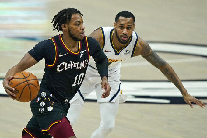 CORRECTS DENVER PLAYER TO MONTE MORRIS, INSTEAD OF WILL BARTON - Cleveland Cavaliers' Darius Garland, left, drives past Denver Nuggets' Monte Morris during the first half of an NBA basketball game Friday, Feb. 19, 2021, in Cleveland. (AP Photo/Tony Dejak)