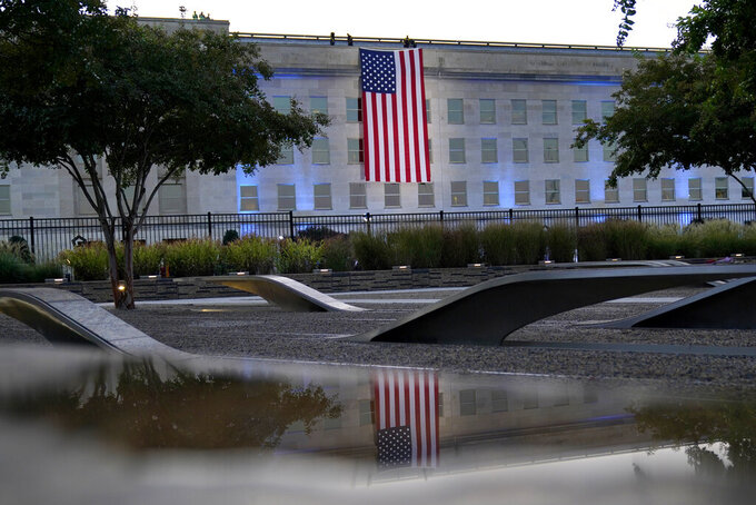 An American flag is unfurled at the Pentagon in Washington, Saturday, Sept. 11, 2021, at sunrise on the morning of the 20th anniversary of the terrorist attacks. The American flag is draped over the site of impact at the Pentagon. In the foreground, the National 9/11 Pentagon Memorial, opened in 2008 adjacent to the site, commemorates the lives lost at the Pentagon and onboard American Airlines Flight 77. (AP Photo/Alex Brandon)