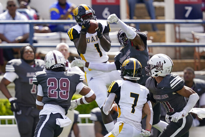 Arkansas-Pine Bluff wide receiver Harry Ballard III (1) catches a pass while surrounded by Alabama A&M defenders during the first half of the Southwestern Athletic Conference NCAA college football game, Saturday, May 1, 2021, in Jackson, Miss. (AP Photo/Rogelio V. Solis)