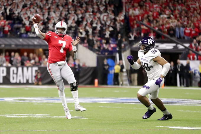 Ohio State quarterback Dwayne Haskins (7) throws a touchdown pass as Northwestern's Earnest Brown IV (98) defends during the first half of the Big Ten championship NCAA college football game, Saturday, Dec. 1, 2018, in Indianapolis. (AP Photo/Michael Conroy)