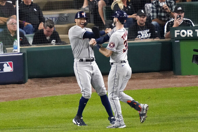 Houston Astros' Kyle Tucker, right, celebrates his two-run home run with Carlos Correa against the Chicago White Sox in the third inning during Game 3 of a baseball American League Division Series Sunday, Oct. 10, 2021, in Chicago. (AP Photo/Charles Rex Arbogast)