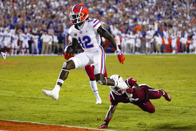 Florida wide receiver Rick Wells (12) jumps into the end zone for a touchdown past Florida Atlantic safety Teja Young during the first half of an NCAA college football game Saturday, Sept. 4, 2021, in Gainesville, Fla. (AP Photo/John Raoux)
