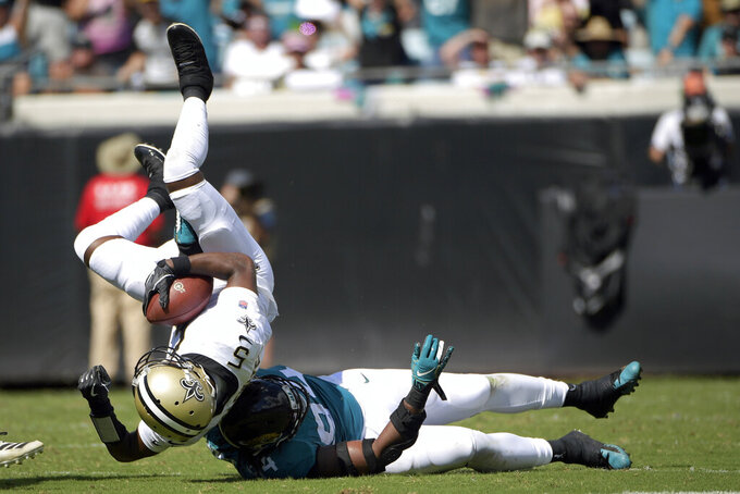 Jacksonville Jaguars defensive end Dawuane Smoot, bottom right, sacks New Orleans Saints quarterback Teddy Bridgewater during the first half of an NFL football game, Sunday, Oct. 13, 2019, in Jacksonville, Fla. (AP Photo/Phelan M. Ebenhack)