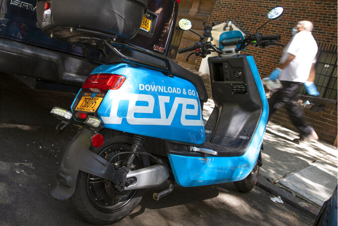 A man passes a parked Revel scooter on New York's Upper West Side, Tuesday, July 28, 2020. The moped sharing startup Revel suspended its New York City service Tuesday, July 28, 2020 after its second customer death in 10 days. The company's blue scooters, which require no training to rent, had been seen as an alternative to taxis and subways during the coronavirus pandemic. (AP Photo/Richard Drew