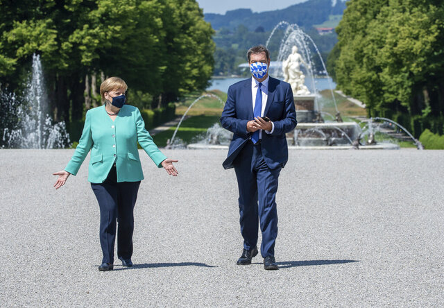German Chancellor Angela, left, and Markus Soeder, right, Governour of the German state of Bavaria, arrive at the Herrechiemsee island, Germany, Tuesday, July 14, 2020. German Chancellor Angela Merkel attends a meeting of the Bavarian state cabinet at the 'Herrenchiemsee' palace. (Peter Kneffel/DPA via AP, Pool)
