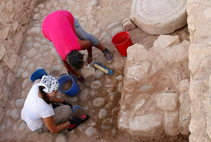 In this photo provided from the Department of Antiquities of Cyprus, on Wednesday, Aug. 14, 2019, Archeologists work at the archeological site area during the 2019 excavation season at Kouklia outside in southwest city of Paphos, Cyprus.  Archaeologists say the discovery of a small clay shard inscribed with a partial inventory of goods at a 2,500 year-old citadel suggests that Cyprus' ancient city states