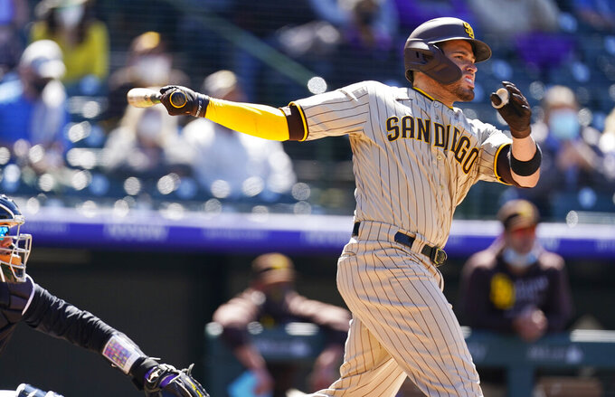 San Diego Padres' Victor Caratini follows the flight of his grand slam off Colorado Rockies relief pitcher Robert Stephenson in the sixth inning of game one of a baseball doubleheader Wednesday, May 12, 2021, in Denver. (AP Photo/David Zalubowski)