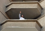 Mahmoud Abu Zaid, a photojournalist known as Shawkan, waves to his neighbors from his home balcony in Cairo, Egypt, Monday, March 4, 2019. Shawkan was released after five years in prison. (AP Photo/Amr Nabil)