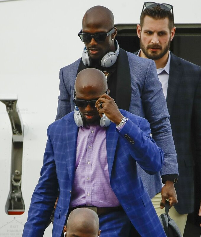 New England Patriots' Devin McCourty, front, and brother Jason McCourty arrive at the Hartsfield-Jackson Atlanta International Airport for the NFL Super Bowl 53 football game Sunday, Jan. 27, 2019, in Atlanta. (AP Photo/Matt Rourke)