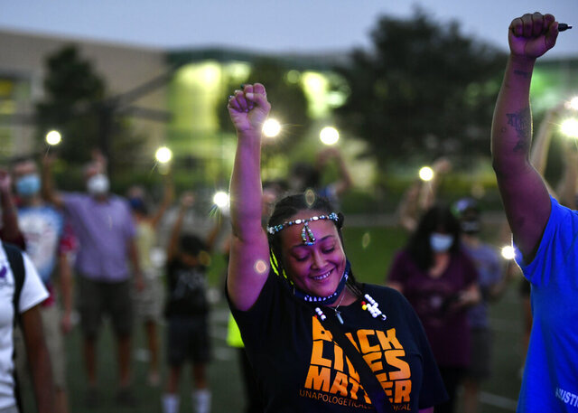 Ebony Wallace holds her fist in the air along with other participants at an event, Gathering in Gratitude presented by Motherhood, held to honor the memory of Elijah McClain, in Denver on Sunday, Aug. 23, 2020. McClain died after being stopped by police last year in the suburb of Aurora. (Helen H. Richardson/The Denver Post via AP)