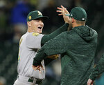 Oakland Athletics' Matt Chapman, left, celebrates the 7-3 win over the Seattle Mariners after a baseball game, Monday, Sept. 24, 2018, in Seattle. (AP Photo/John Froschauer)