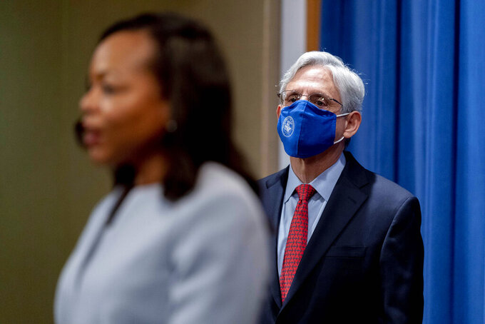 Attorney General Merrick Garland listens as Assistant Attorney General for Civil Rights Kristen Clarke, foreground, speaks at a news conference at the Department of Justice in Washington, Thursday, Aug. 5, 2021, to announce that the Department of Justice is opening an investigation into the city of Phoenix and the Phoenix Police Department. (AP Photo/Andrew Harnik)