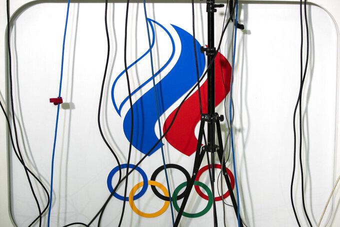 FILE - In this file photo dated Monday, Dec. 9, 2019, microphone wires above a logo of the Russian Olympic Committee during President of the Russian Olympic Committee Stanislav Pozdnyakov's news conference in Moscow, Russia. Russia was banned Thursday Dec. 17, 2020 from using its name, flag and anthem at the next two Olympics or at any world championships for the next two years. The Court of Arbitration for Sport's ruling also blocked Russia from bidding to host major sporting events for two years. (AP Photo/Pavel Golovkin, File)
